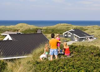 Eine Familie genießt die Aussicht von einem Ferienhaus hinter dem Strand von Saltum