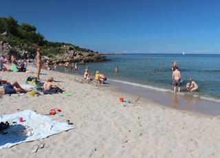 Den dejlige badestrand med børnevenligt vand i Sandkås er omgivet af klipper