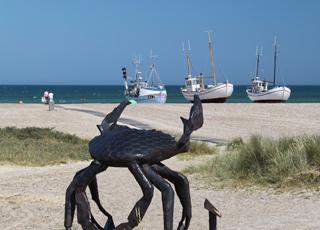 Eiserne Skulptur einer Krabbe, das Wahrzeichen von Slettestrand, vor den Fischerbooten am Strand