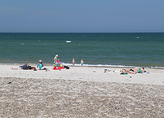 Badegäste in den Wellen am Strand von Slettestrand