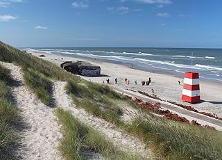 Livreddertårn, bunkere og badegæster på Søndervigs brede sandstrand