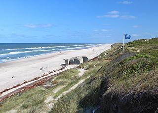 Det blå flag vajer over Søndervigs sandstrand med bunkere og dejligt badevand