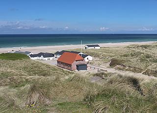 Das Rettungshaus und die weißen Fischerhäuser von der hohen Düne hinter dem Strand von  Stenbjerg aus gesehen