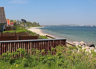 Udsigt over stranden og det klare badevand fra sommerhusene i ferieområdet Strib