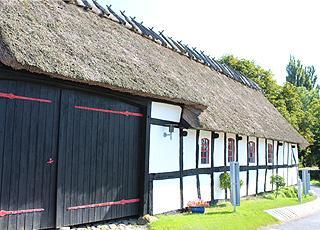Historisches Fachwerkhaus mit Reetdach hinter den Ferienhäusern in Tårup