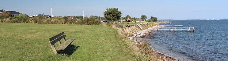 Aussichtsbank in einer Grünanlage bei den Ferienhäusern und dem Strand in Tårup