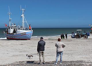 En af fiskerbådene, som trækkes op med traktor, i Thorup Strand