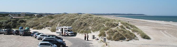 Breiter Sandstrand in Tranum und Ferienhäuser in den Dünen hinter dem Strand