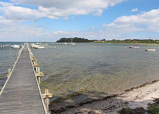 Lang bådebro ved Stranden i Varnæs og udsigt til Varnæs Hoved