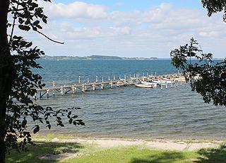 Udsigt til stranden og bådebroen fra bakken bag kysten i Varnæs