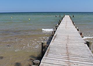 Klart vand ved den lange badebro på stranden i ferieområdet Vejlby Fed