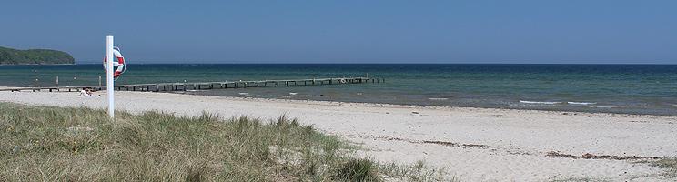 Lang badebro ved den brede sandstrand i sommerhusområdet Vejlby Fed