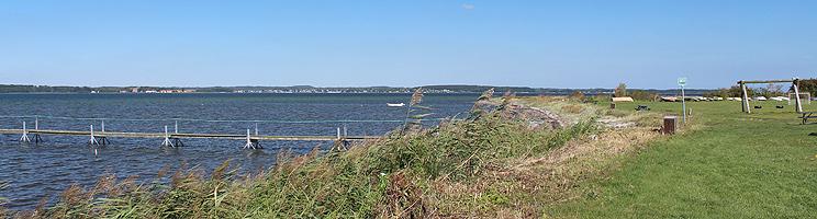 Grønne områder med fodboldmål og legeplads bag stranden i Vemmenæs