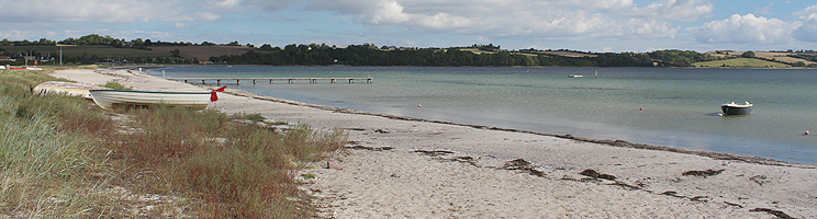 Fin, bred sandstrand med badebro og klart badevand i sommerhusområdet Vemmingbund