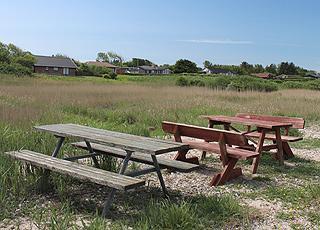 Tische und Bänke am Strand unterhalb der Ferienhäuser in Vinderup