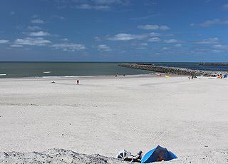 Ein Sommertag am breiten Sandstrand mit der Mole in Hvide Sande