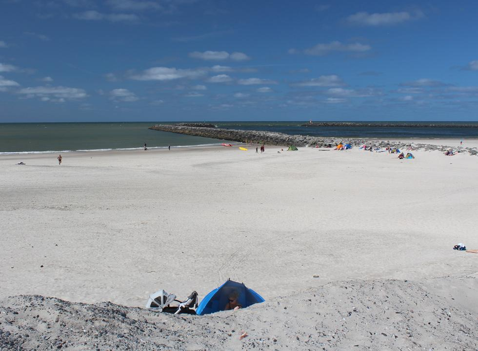 En sommerdag på den brede sandstrand med mole i Hvide Sande