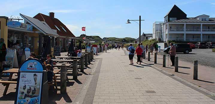 Gågade i ferieby med iskiosker og butikker til venstre, ferielejligheder til højre og klitter i baggrunden.
