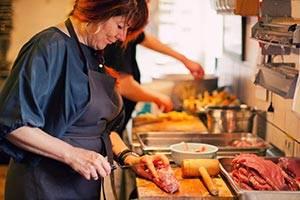 Frau schneidet Fleisch