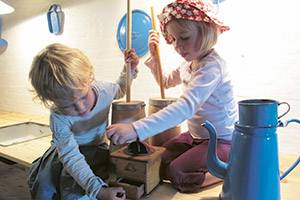 Two children play in old-fashioned kitchen