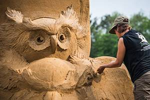 Man makes a sculpture of an owl with sand