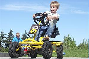 Boy grapples with the 4-wheel bicycles of the park