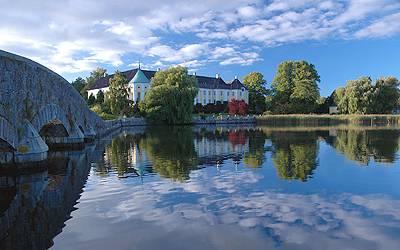 Gavnø Slot og slotshaven spejler sig i søen