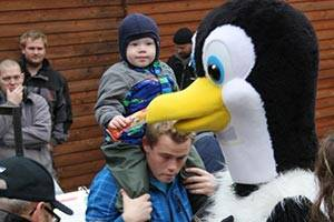 Child saying hello to a penguin mascot