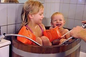Twee kinderen in een houten badkuip