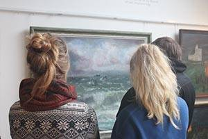 Visitors admire a painting