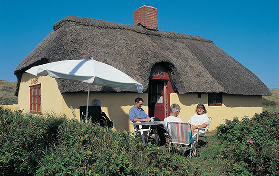 Holiday idyll - being together and relaxation in the sun by the holiday home.