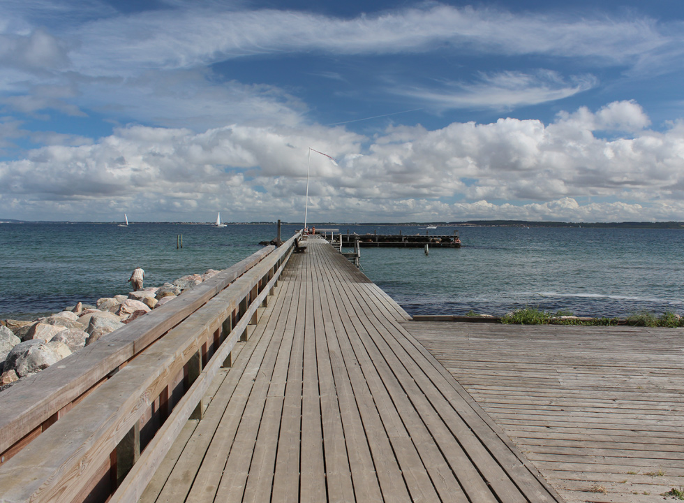 A family swims at the end of the long bathing jetty in Ålsgårde