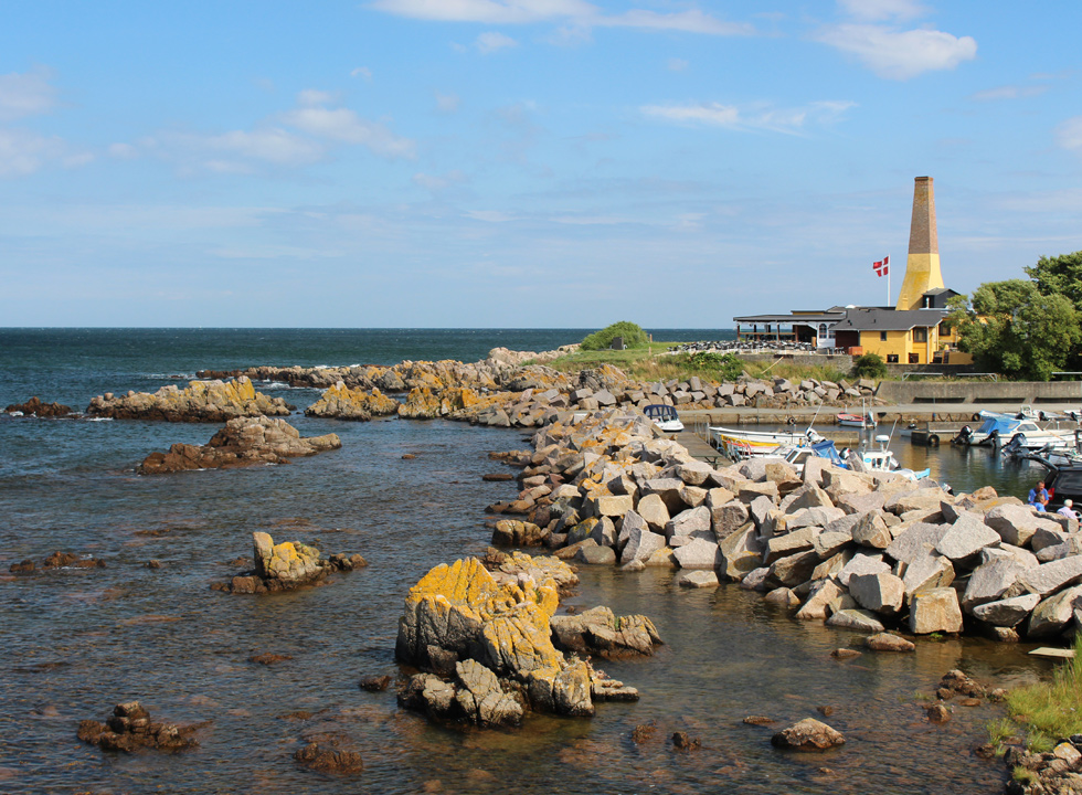View of the rocky coast and the ship harbour towards the smokehouse, Allinge Røgeri, from Domen