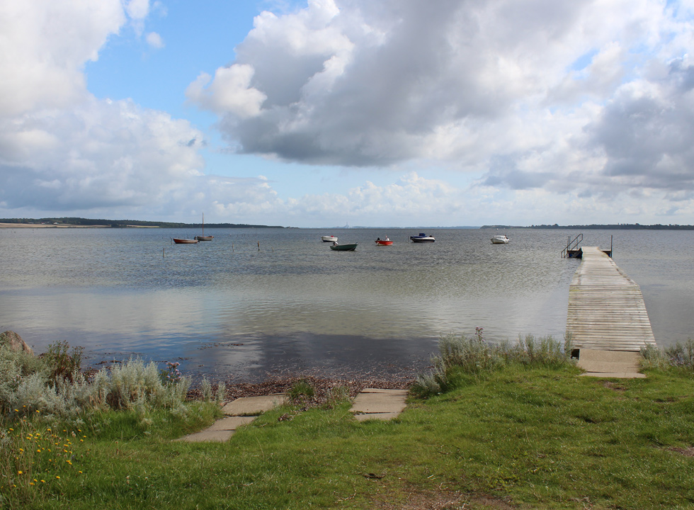 Small boats on the water, next to the bathing jetty, in the holiday home area Atterup