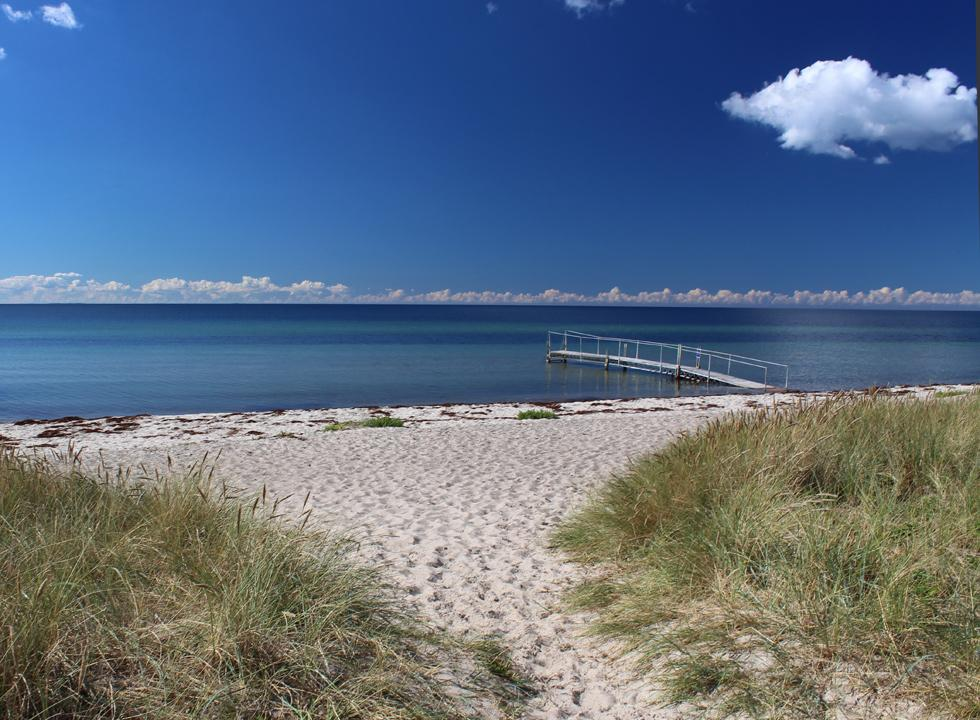 Bathing jetty by the inviting sandy beach with clear bathing water in Bjerge Nordstrand
