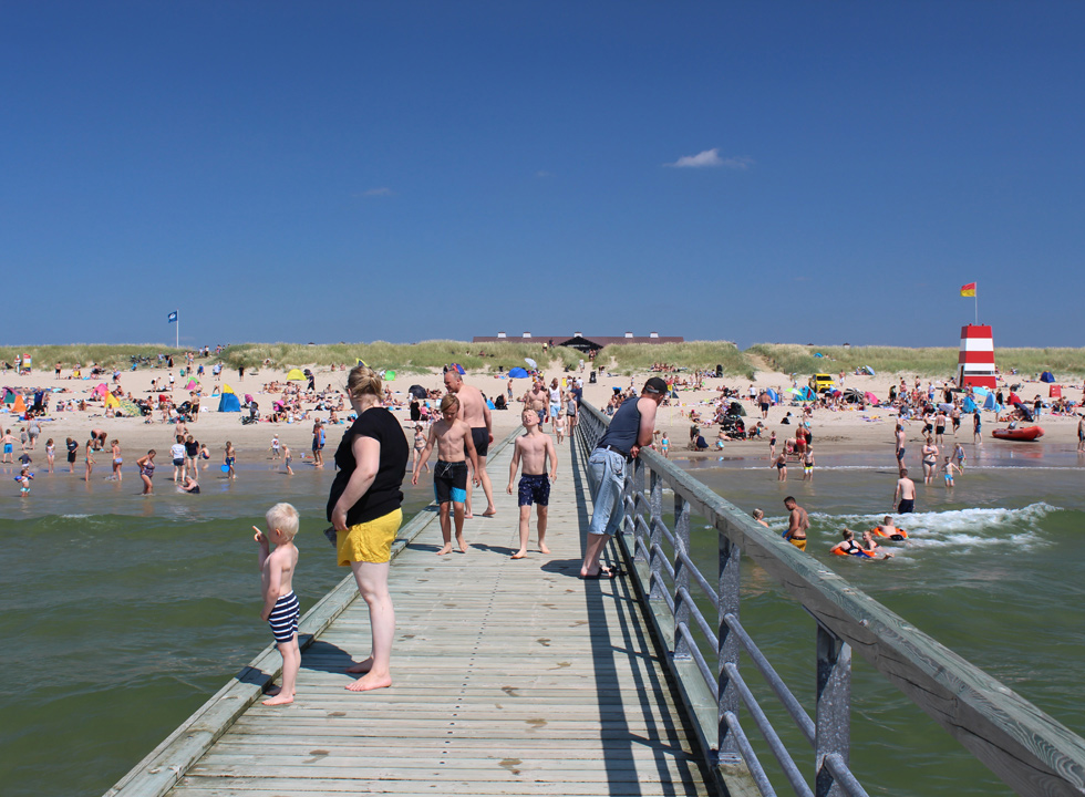 Bathers on the long bathing jetty by the beach Hvidbjerg Strand in Blaavand