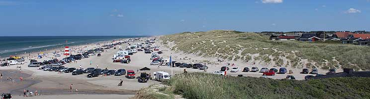 Summer day on the beach of Blokhus with dunes, North Sea, bathers and holiday homes