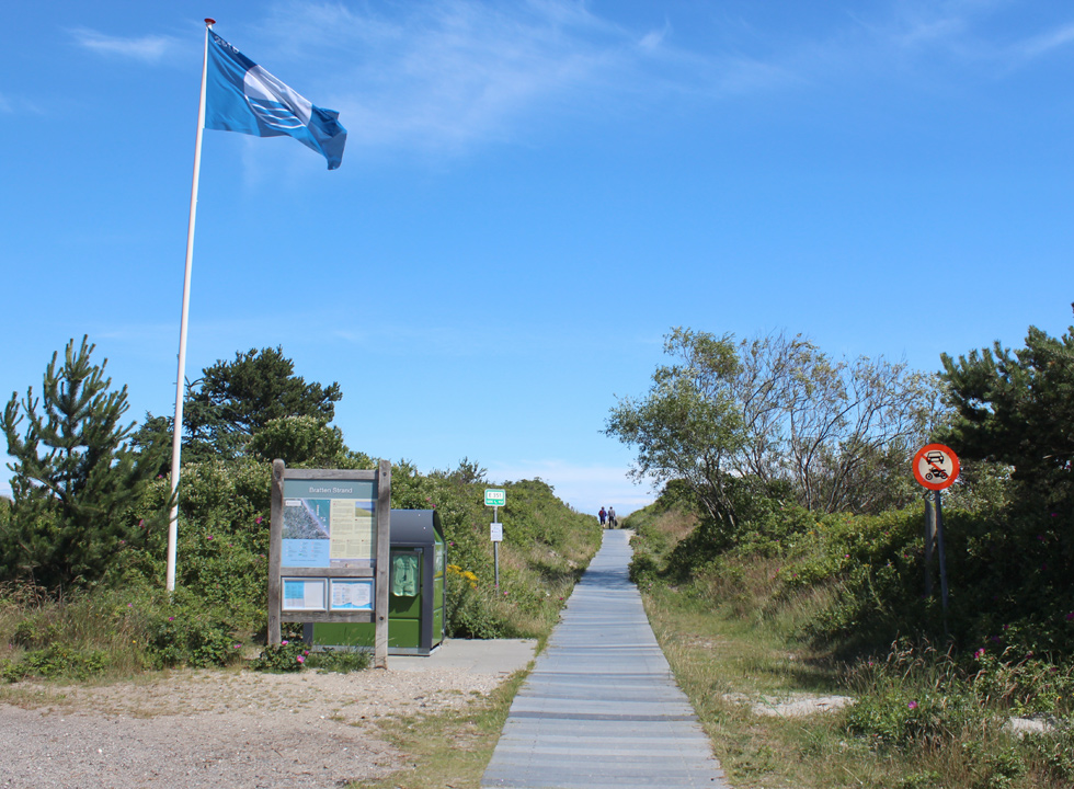 Blue flag at the beginning of the path, which leads to the beach in Bratten