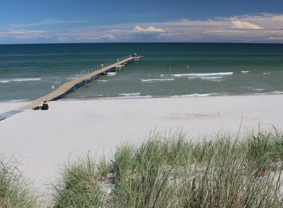 View of the beach and the bathing jetty from the dunes in the holiday area Bratten