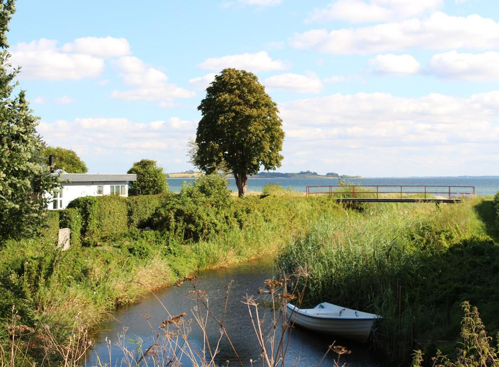 The stream flows past a holiday home in Diernæs and out into the sea