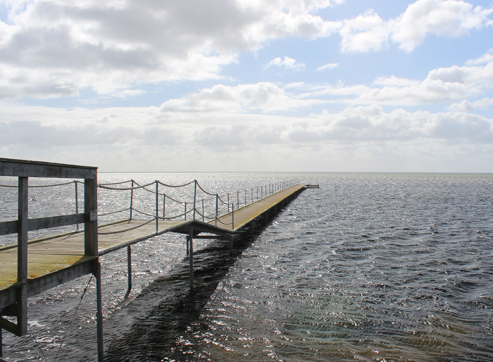 Long bathing jetty off the coast in the holiday home area Dokkedal