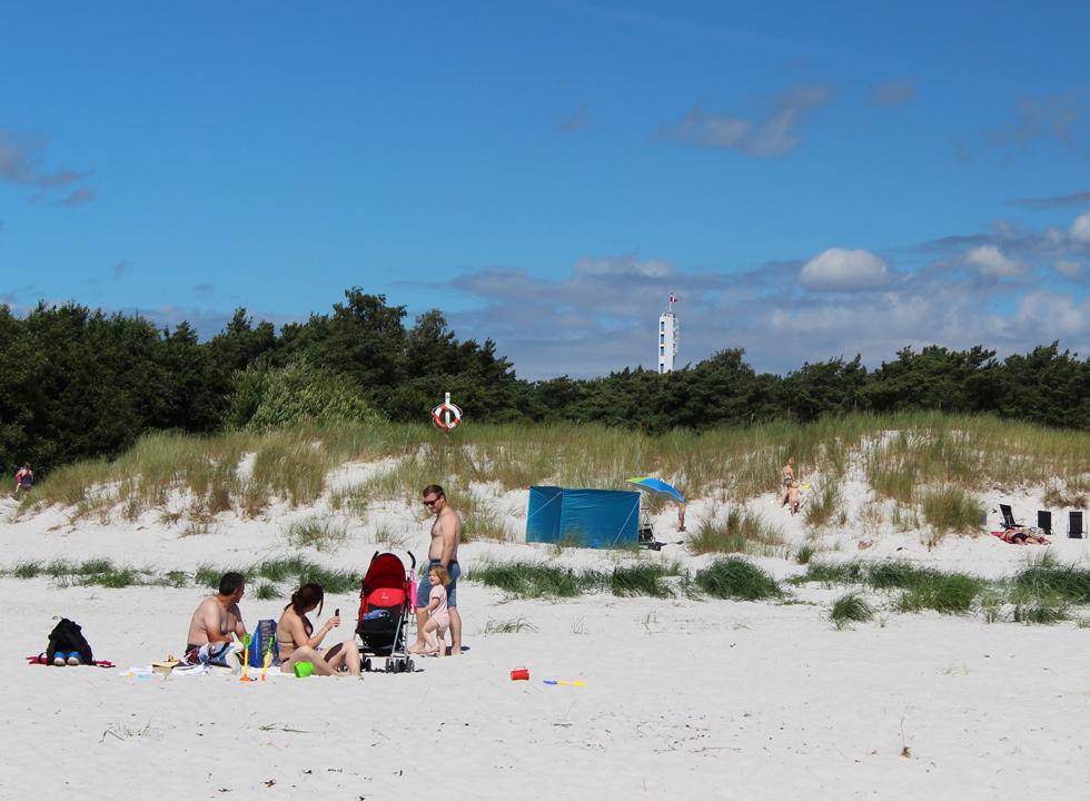 Bathers on the beach of Dueodde with the tower, Bornholmertårnet, in the background
