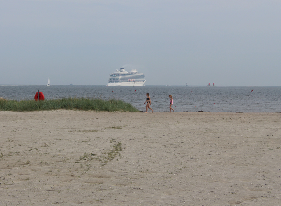 A cruise ship sails close past the bathing beach in Egense