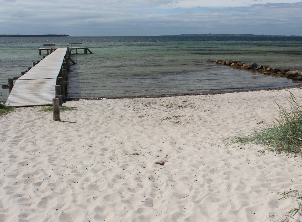 A long bathing jetty leads you out into the shallow and clear water in Egsmark Strand