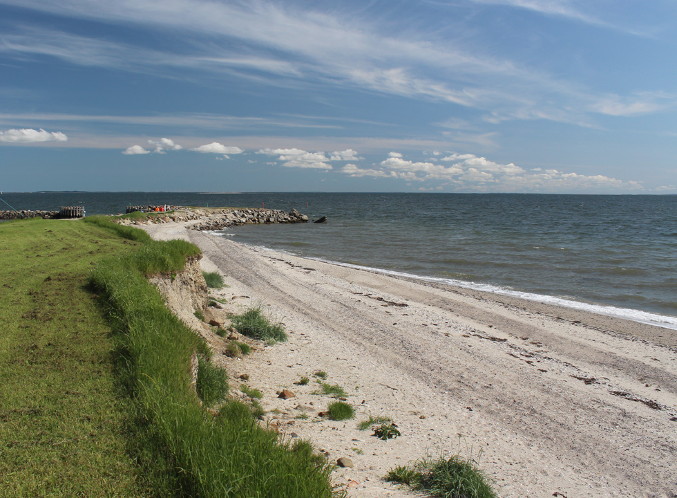 View of the sea and the bathing beach from the green surroundings behind the shore in Ejerslev, Mors