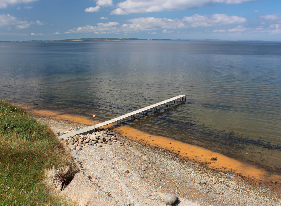 The bathing jetty, which leads out in the clear water in the holiday area Ertebølle