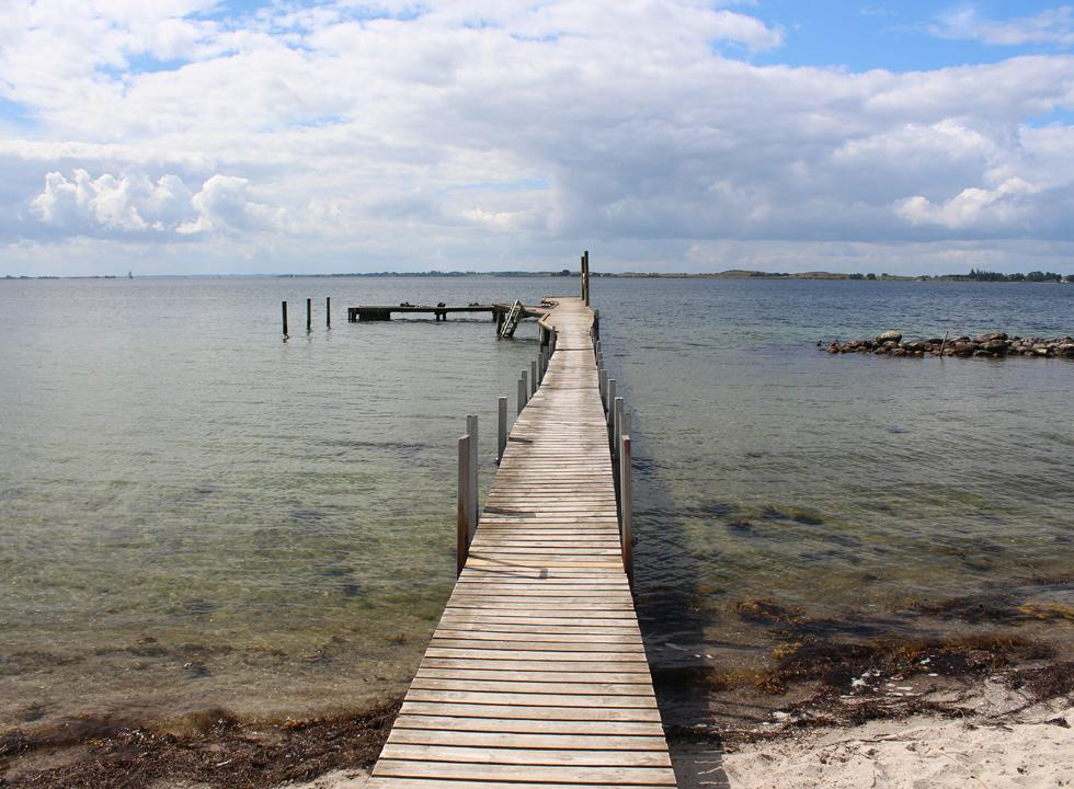 The bathing jetty leads you far out in the clear bathing water in Fåborg