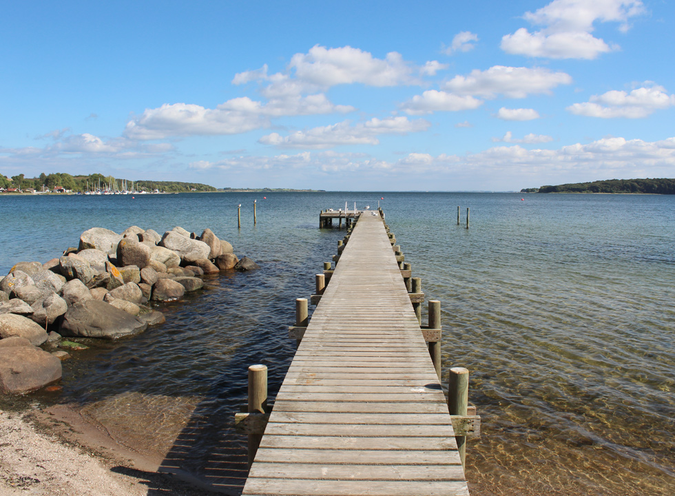 Long bathing jetty in the clear water by the bathing beach in Genner Strand