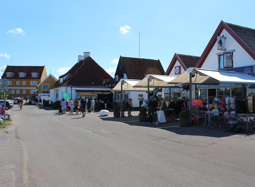 Street with shops and eateries by the harbour in Gilleleje