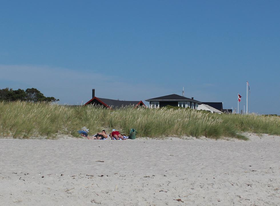 Relaxation on the beach, below the dunes and the holiday homes in Grenå Strand